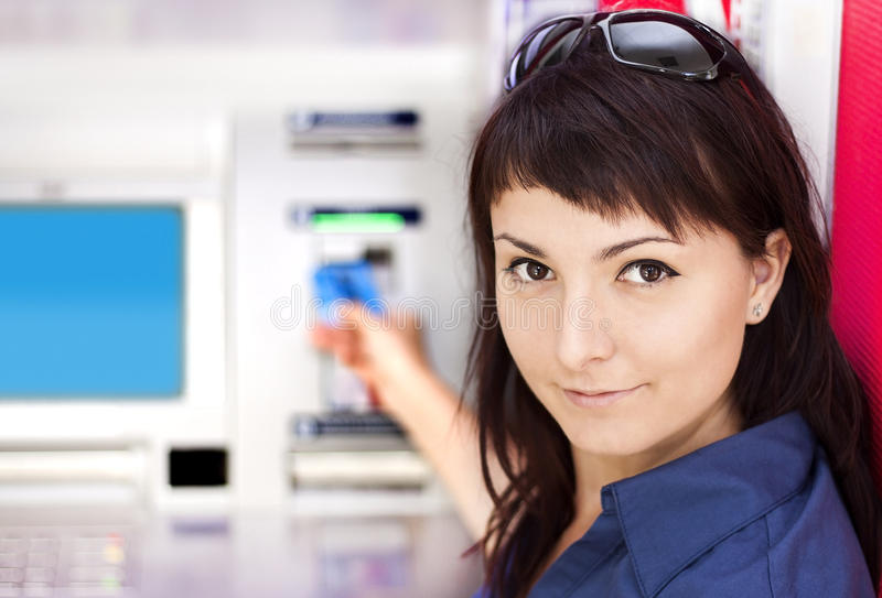 Woman withdrawing money from credit card at ATM stock photo