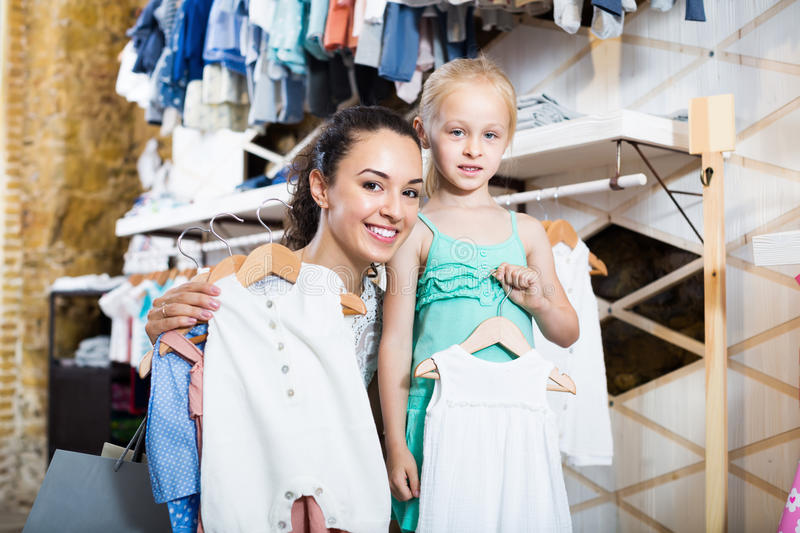 Woman withl girl holding white clothes in kids boutique stock photos