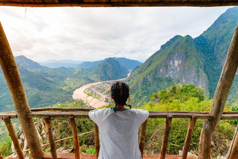Woman on wooden balcony conquering mountain top at Nong Khiaw Nam Ou River valley Laos mature people traveling millenials concept. Travel destination in South royalty free stock photos