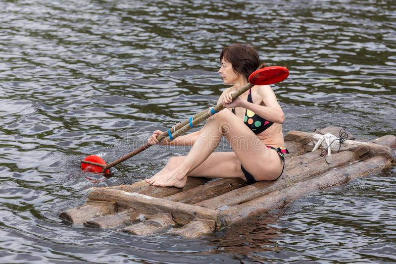 Woman on a wooden raft royalty free stock image