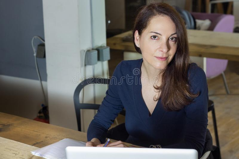 Adult woman at her working place looking camera. Woman on a wooden table looking at camera with confidence holding a pen at her working place royalty free stock photo