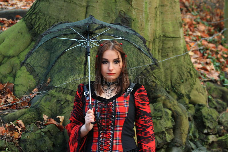 Woman in the woods with umbrella stock photo