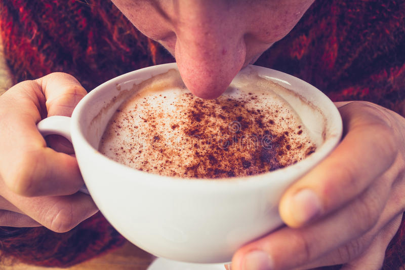 Woman in wool jumper drinking coffee on cold day stock photography