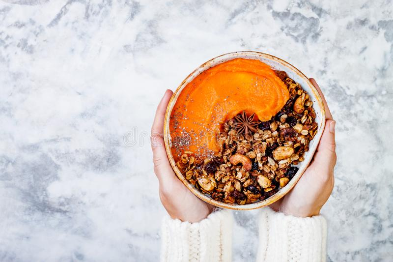 Woman in woolen sweater holding bowl with cinnamon granola, coconut yogurt, chia seeds and pumpkin puree. Healthy vegan smoothie. Woman in woolen sweater holding stock images