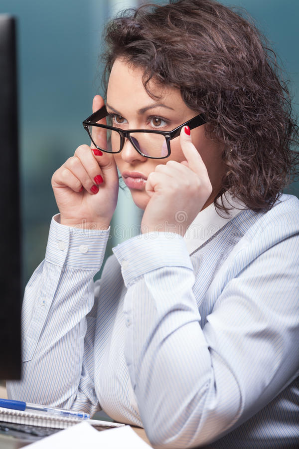 Woman at work. Concentrated beautiful woman at the office royalty free stock image