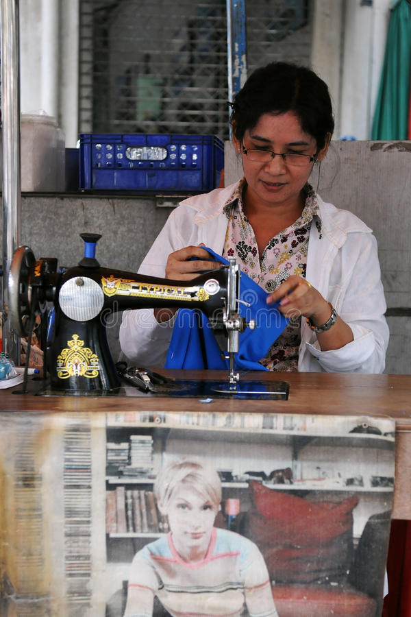 Woman at Work in a Garments Shop. Woman operates a sewing machine in a garments factory on Jan 12, 2011 in Bangkok, Thailand. Textile and clothing manufacturing stock photos