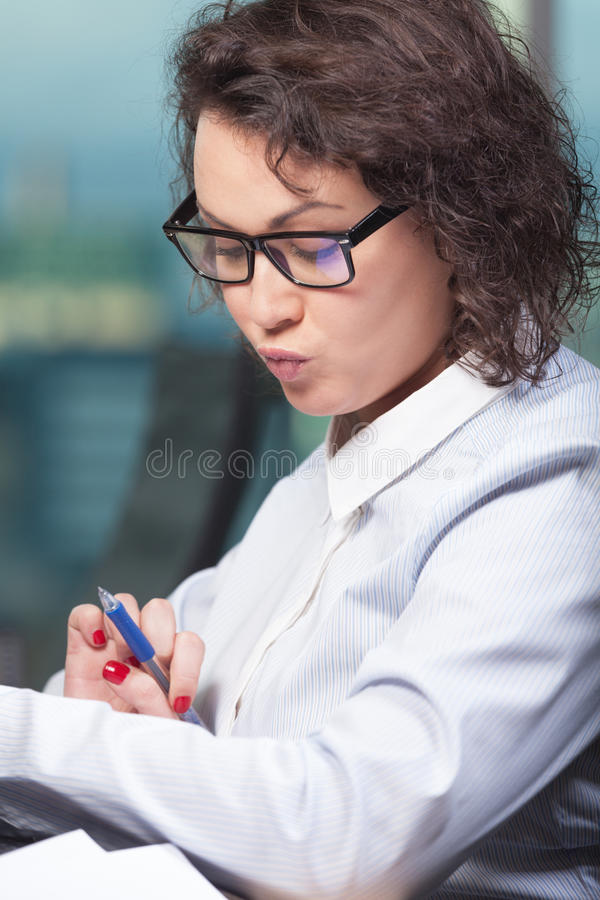 Woman at work. Smart and intelligent woman at work at the office royalty free stock photography