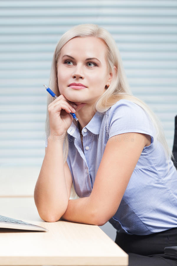 Woman at work. Thoughtful and beautiful woman at work royalty free stock photos