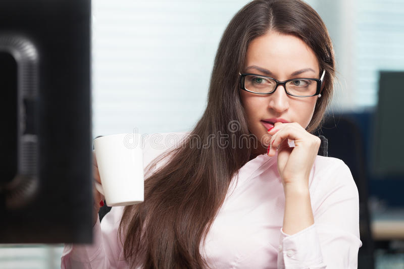Woman at work. Thoughtful neautiful woman at the office solving problem royalty free stock photo