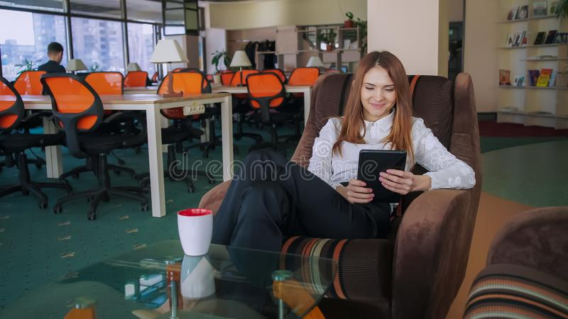 Woman At Work Watching Photo On The Tablet And Laugh. stock photo