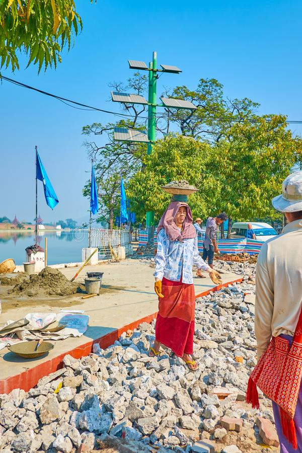 The woman worker carry the stones, Mandalay, Myanmar. MANDALAY, MYANMAR - FEBRUARY 23, 2018: The woman worker carry the plate with cement on her head during road royalty free stock photos