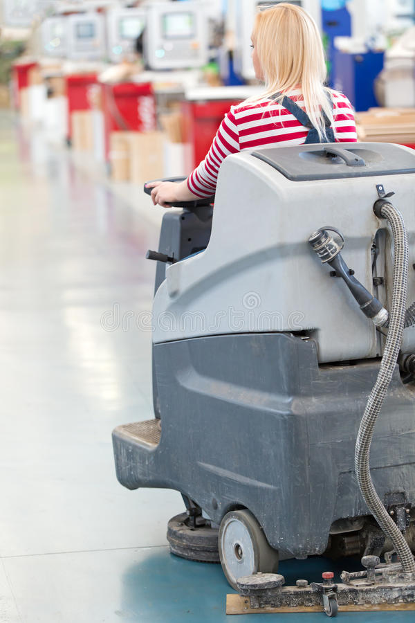 Woman worker cleaning factory workshop floor. With washing vacuum cleaner royalty free stock photo