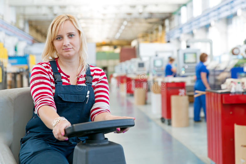 Woman worker cleaning factory workshop floor. With washing vacuum cleaner stock image