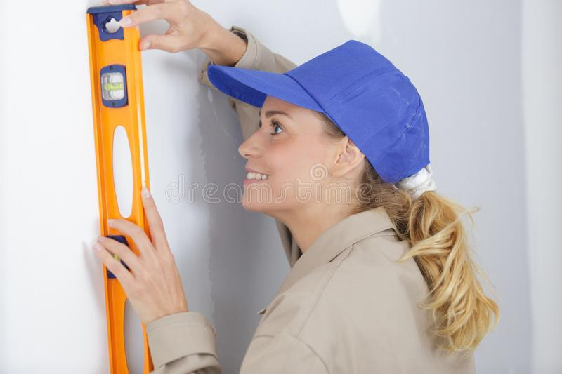 Woman worker leaning spirit level on wall stock image