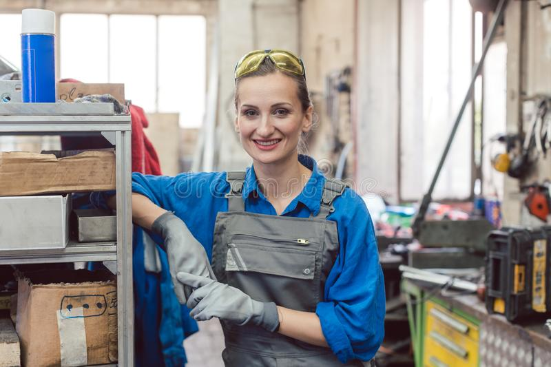 Woman worker in metal workshop looking into camera stock photography
