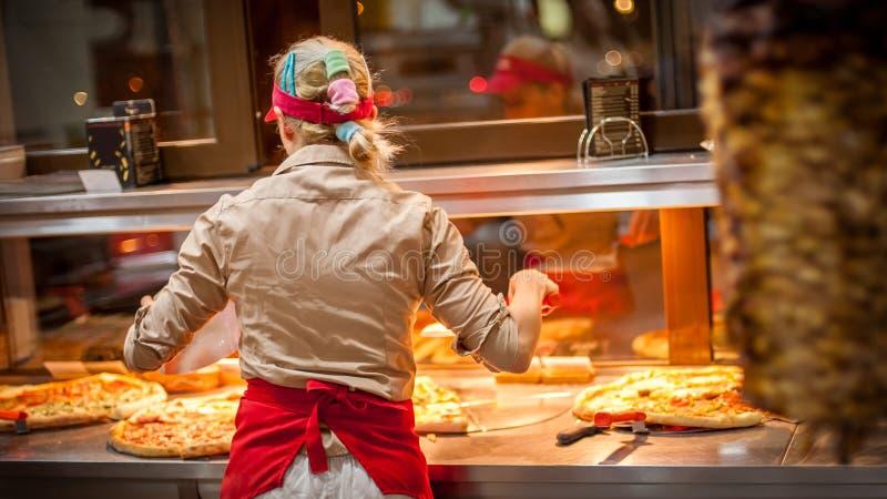 Woman worker selling pizza in fast food restaurant. Rear view. Tasty italian food stock photo