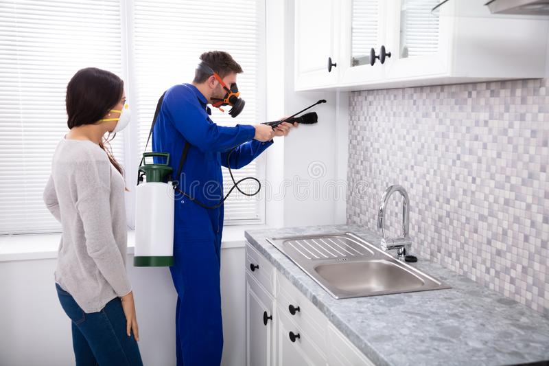 Woman And Worker Spraying Pesticide In Kitchen. Pest Control Worker And Woman Spraying Pesticide With Torch In Kitchen stock images