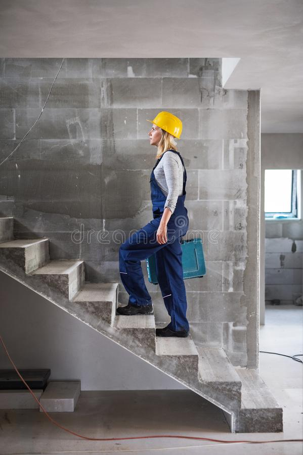 Woman worker with a tool box walking up the stairs on the construction site. stock image
