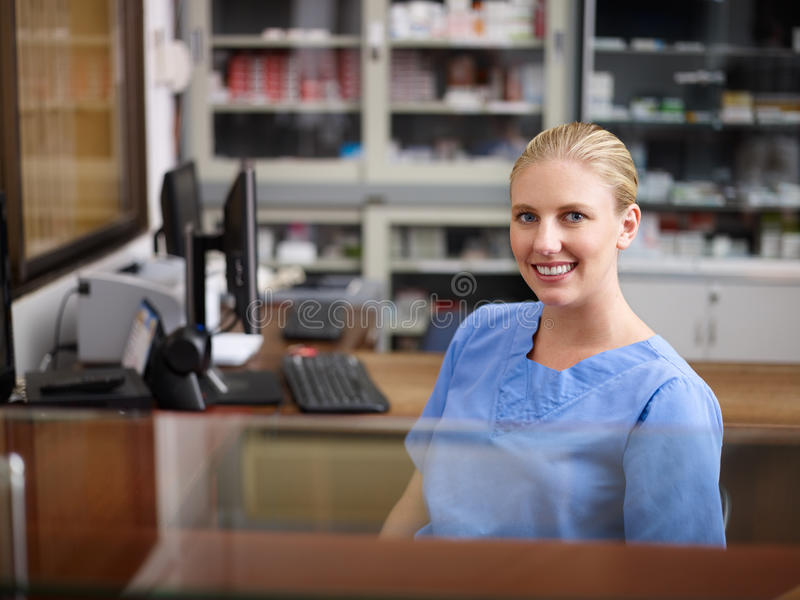Woman working as nurse at reception desk in clinic. Young woman at work as receptionist and nurse in hospital, looking at camera royalty free stock photo