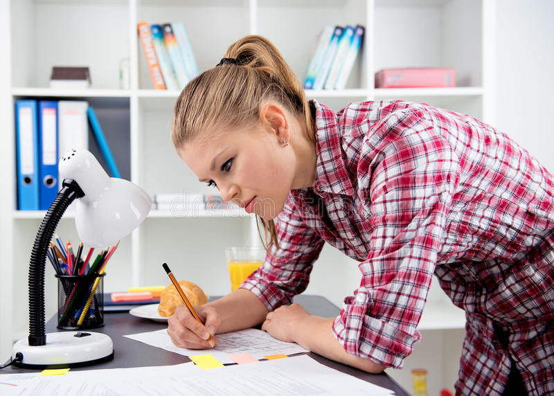 Woman working during breakfast. Female engineer drawing sketch of building working at home. Young architect constructor studying blueprint at the desk royalty free stock photography