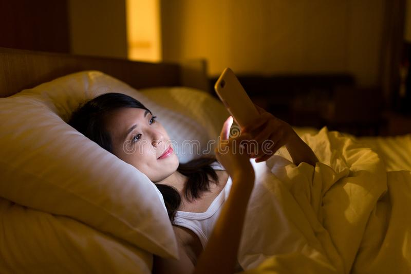 Woman working on cellphone and lying on bed at night royalty free stock images