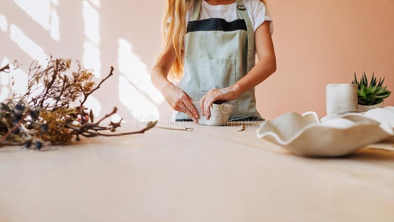 Woman working with clay in her studio. Hands of woman molding a dish. n stock photo