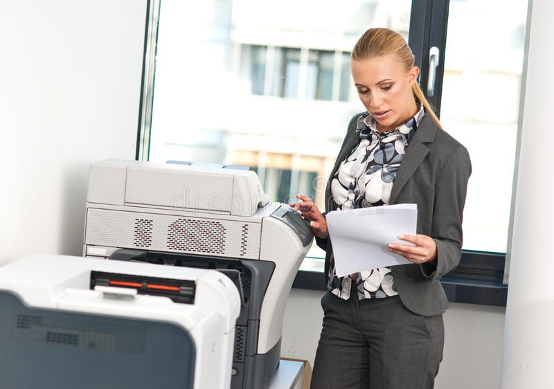 Woman working on copy machine stock photo