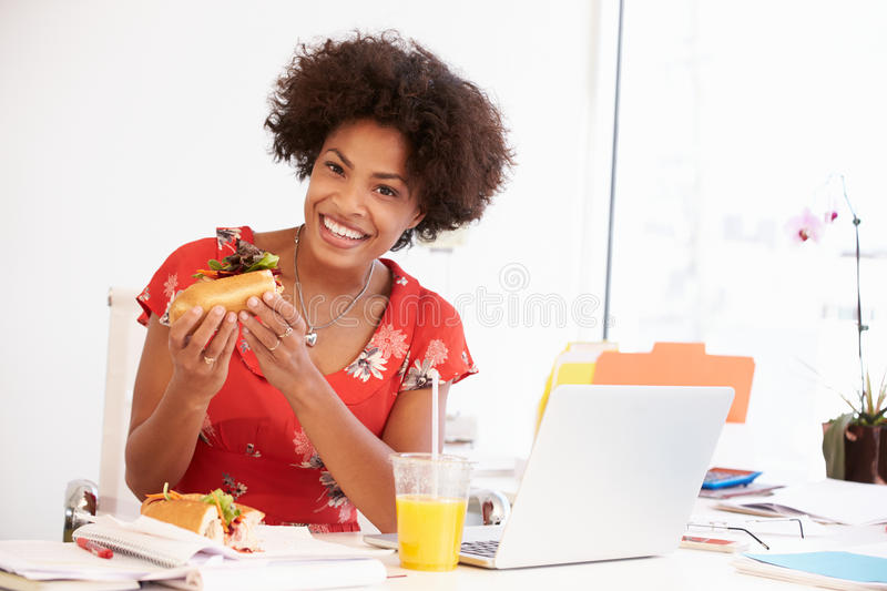 Woman Working In Design Studio Having Lunch At Desk stock photography