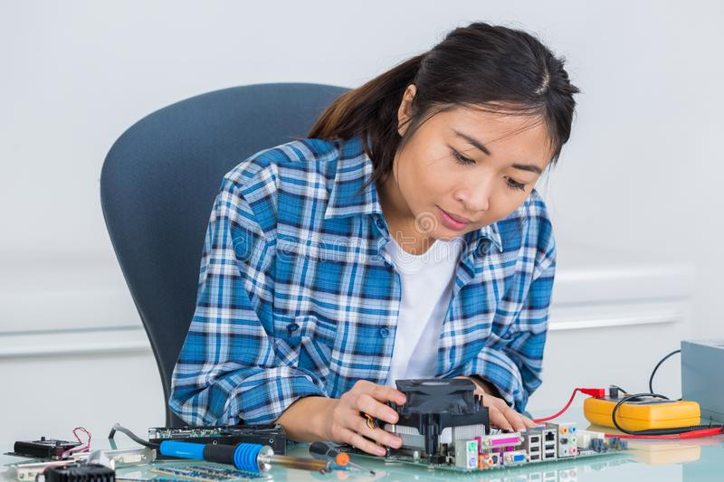 Woman working on electronics components. Repair stock photography