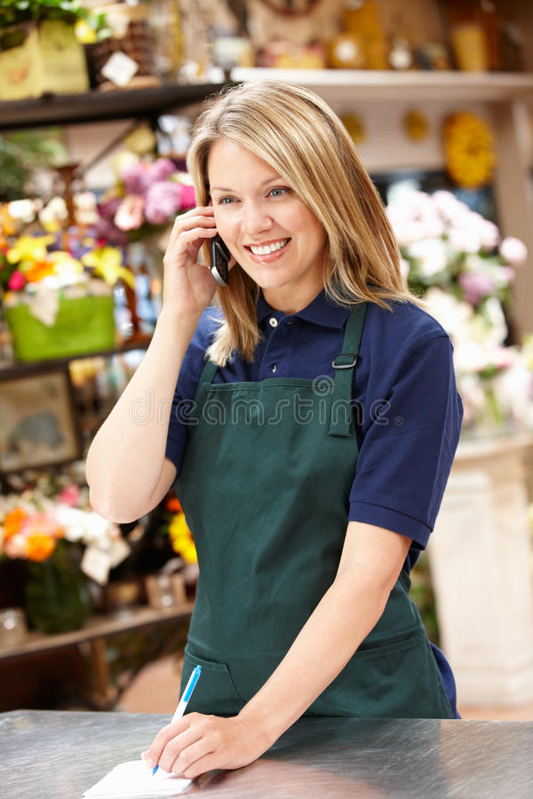 Woman working in florist on phone. Happy woman working in florist on phone smiling off camera stock image