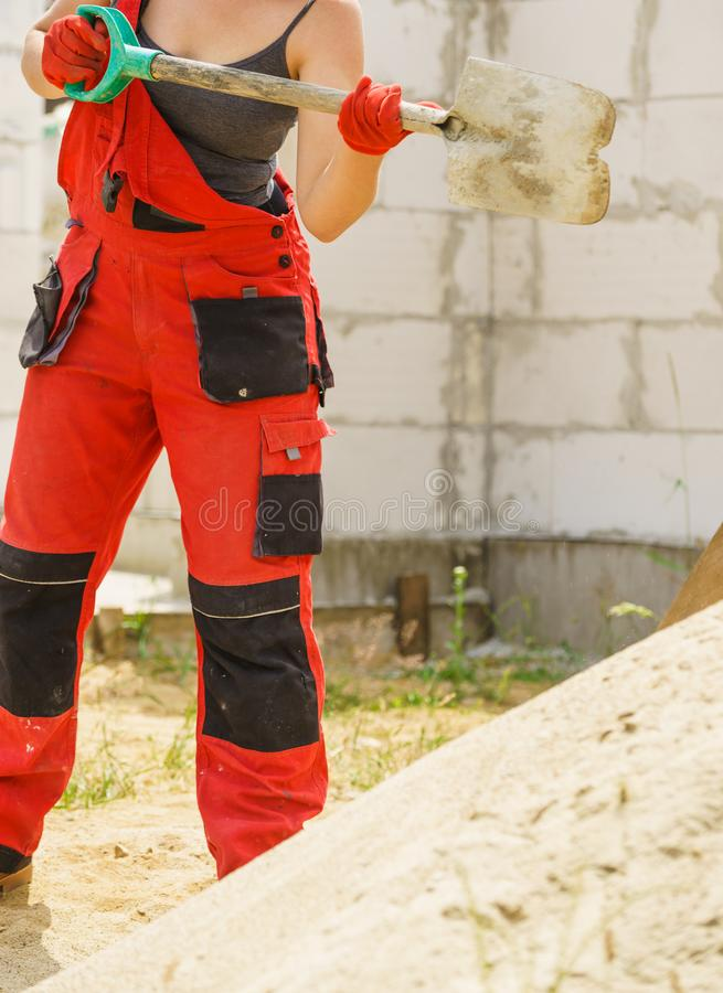 Woman using shovel on constriction site stock photo
