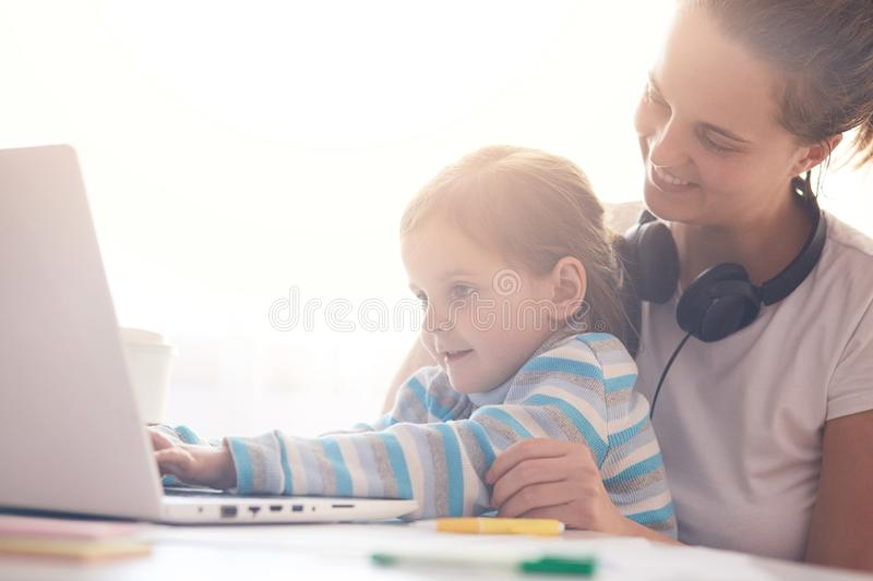 Woman working on her lap top at home in her bedroom and holding her daughter on her knees, mom and her little child waching. Cartoons together online, using royalty free stock image