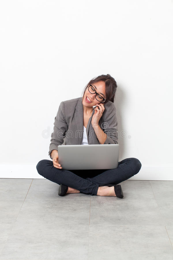 Woman working on her laptop, talking on phone sitting on floor royalty free stock photos