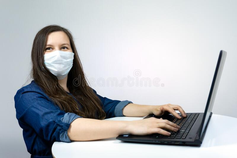 Woman working at home with medical mask on face. coronavirus quarantine remote home working concept.  stock photography