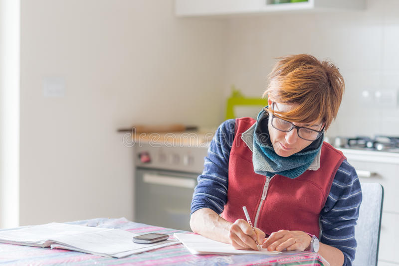 Woman working at home, reading and handwriting documents stock image