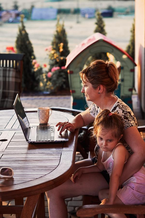 Woman working at home, using portable computer. Mother working at home, using portable computer, sitting on patio with her daughter on summer day stock photography
