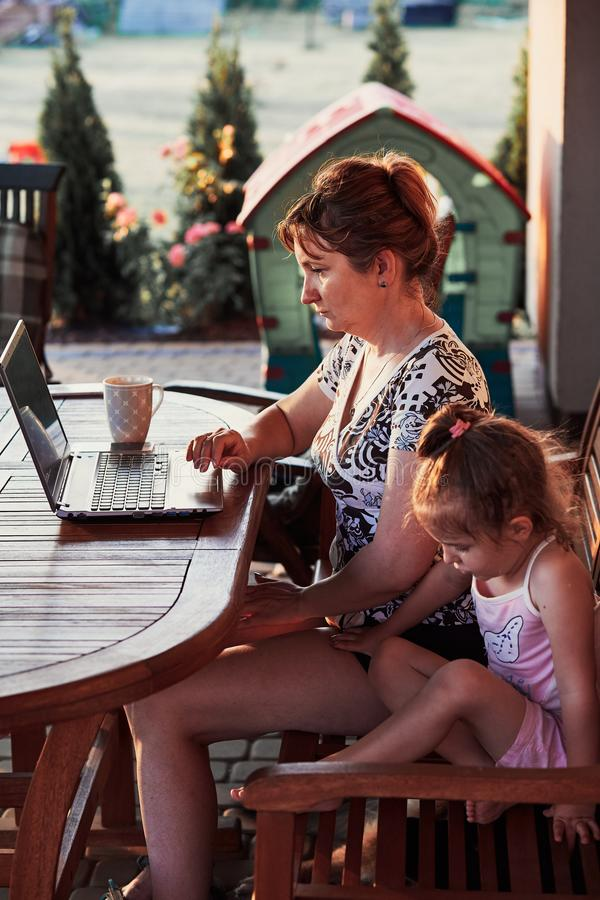 Woman working at home, using portable computer. Mother working at home, using portable computer, sitting on patio with her daughter on summer day stock photo