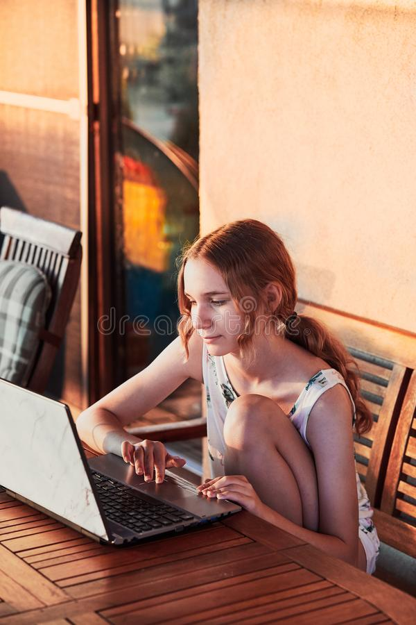 Woman working at home, using portable computer. Sitting on patio on summer day stock photos