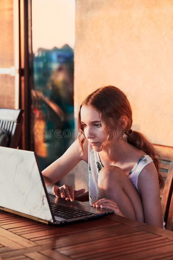 Woman working at home, using portable computer. Sitting on patio on summer day stock photography
