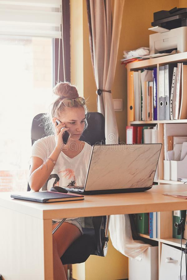 Woman working at home, using portable computer. Young woman working at home, using portable computer, sitting at desk in home office. Candid people, real moments stock image