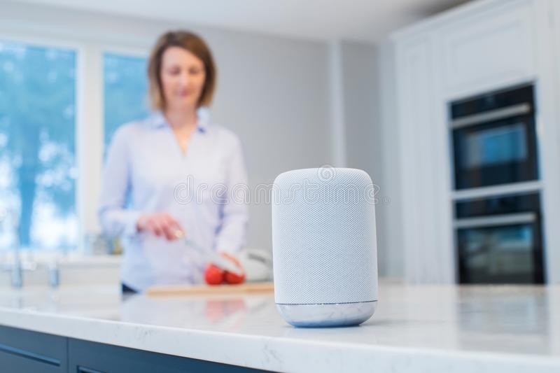 Woman Working In Kitchen With Smart Speaker In Foreground stock photo