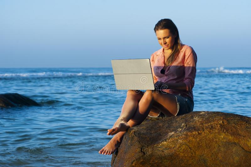 Woman working on laptop on beach at sea royalty free stock photo