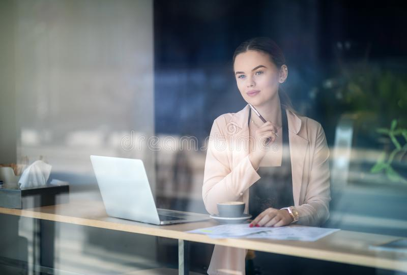 Woman working on laptop at coffee shop. Window Reflexions. Shot of a young woman using a laptop in a cafe.  royalty free stock images