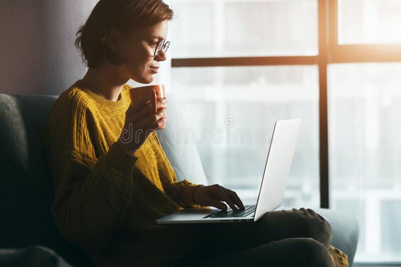 Woman working with laptop and coffee or tea at home quarantine stock photo