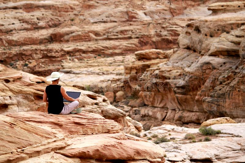 Woman working on laptop computer high up on rocks. stock photo