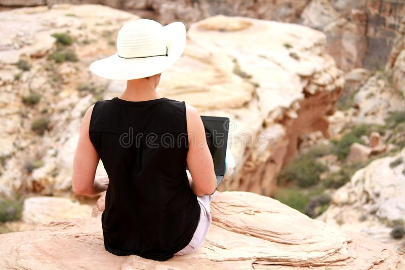 Woman working on laptop computer high up on rocks. royalty free stock images