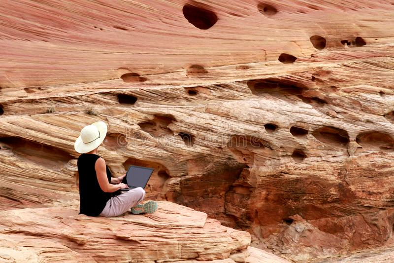 Woman working on laptop computer high up on rocks. royalty free stock image