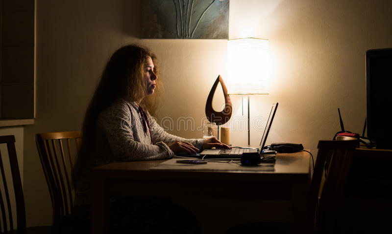 Woman working with laptop computer at night royalty free stock photos