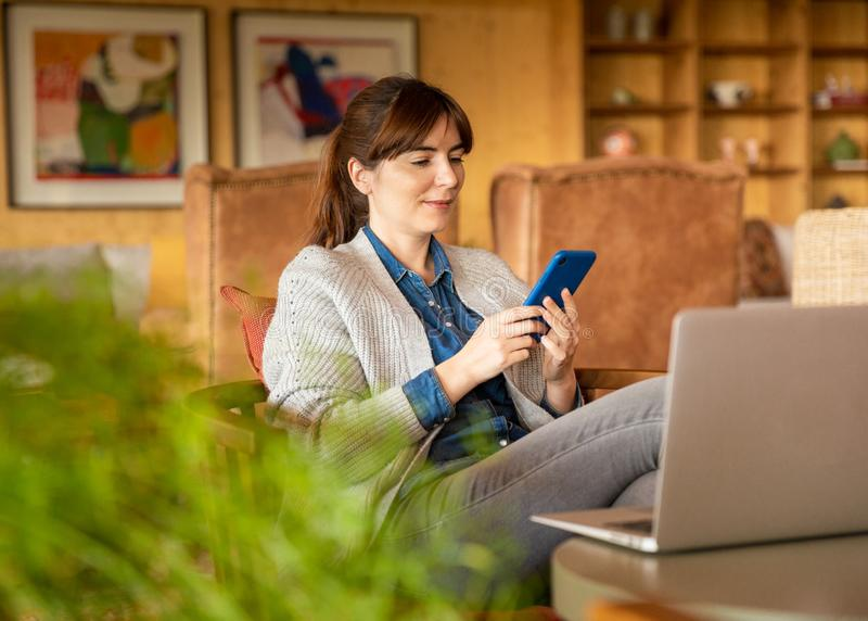 Woman working on a laptop. On a cozy space royalty free stock images