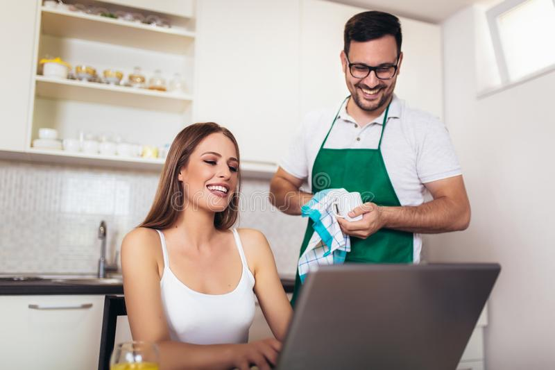 Woman working on laptop in kitchen as boyfriend prepares meal royalty free stock photography